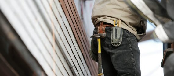 Partial view of person wearing jeans, workshirt, and toolbelt with hammer hanging from it