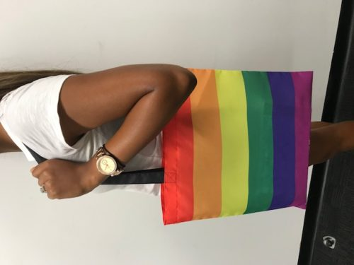 Image of tote bag in rainbow pride flag colours, hanging from shoulder of brown-skinned person.