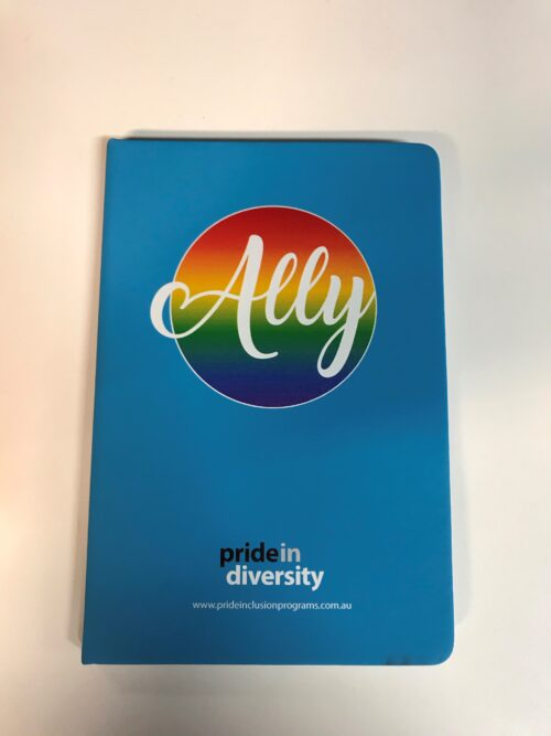 Image is of a light blue notebook with a large round rainbow emblem behind the word Ally in white centred towards the top. A small Pride in Diversity logo is at the bottom of the cover.