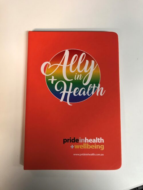 Image is of a bright orange notebook with a large round rainbow emblem behind the words Ally in Health inwhite centred towards the top. A small Pride in Health + Wellbeing logo is at the bottom of the cover.