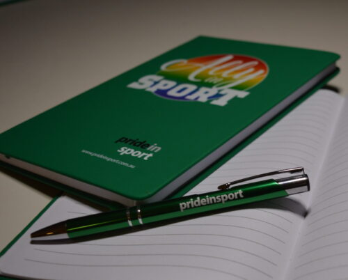 image shows a green and silver pen with the words Pride in Sport on the barrel, resting on the lined page of an open book, with another green notebook resting above it showing a green cover with the words Ally in Sport
